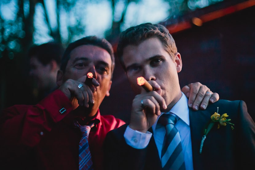 groom and father share celebratory cigar